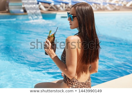 cheerful women drinking cocktails and laughing near swimming pool stock photo © deandrobot