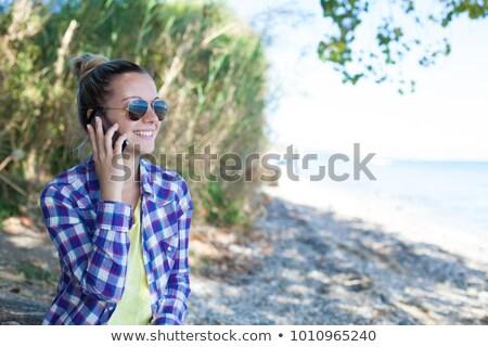 Caucasian female hands using mobile phone on seaside vacation Stock photo © stevanovicigor