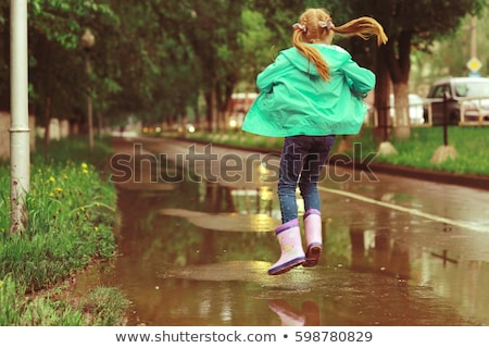Stockfoto: Rain City Happy Girl Jumping In The Puddle