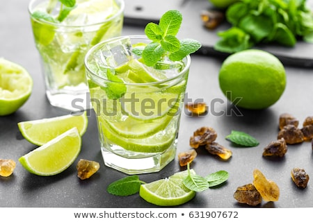 Summer mint lime refreshing cocktail mojito with rum and ice in glass on black background top view Stock photo © yelenayemchuk