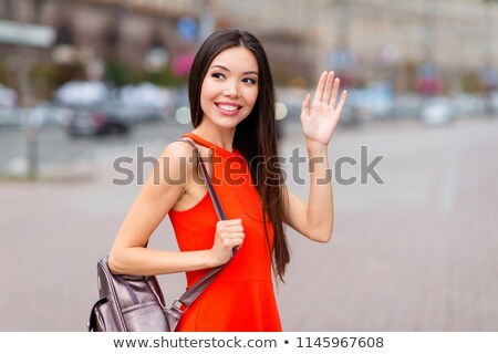 Young asian traveler waving her hand. Stock photo © RAStudio