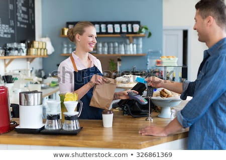 Woman standing at counter in restaurant serving customer and smi Stock photo © monkey_business