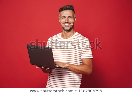 Image of delighted man in striped t-shirt smiling while holding  Stock photo © deandrobot