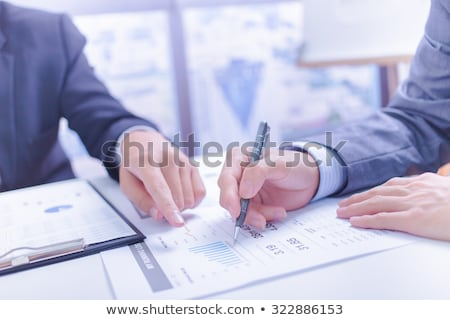 Stock photo: Two businessmen looking at report and having a discussion in off
