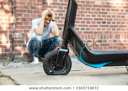 stressed man looking at flat tire on e scooter stock photo © andreypopov