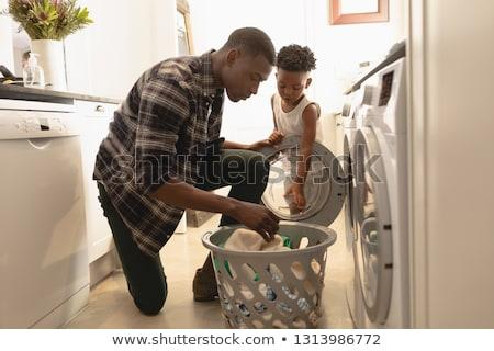 side view of african american man washing clothes in washing machine at home stock photo © wavebreak_media