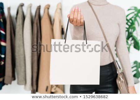 Young stylish female shopper with handbag standing in front of camera Stock photo © pressmaster