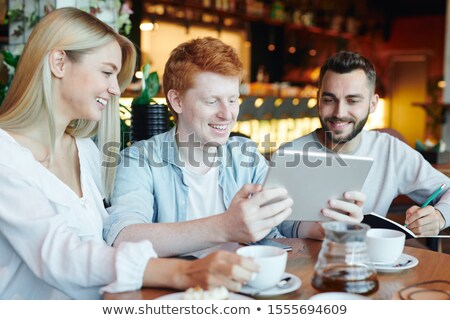 Happy groupmates looking at touchpad display held by one of guys in cafe Stock photo © pressmaster