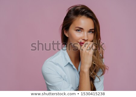 Photo of self assured attractive woman with long hair, keeps hand on lips, dressed in blue shirt, lo Stock photo © vkstudio