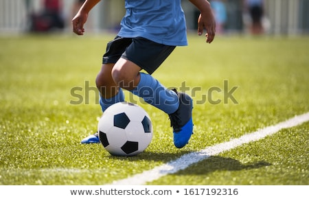 African American young boy playing soccer in a stadium pitch. Child running with soccer ball along t Stock photo © matimix