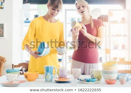Women buying ceramic dishes in a workshop Stock photo © Kzenon