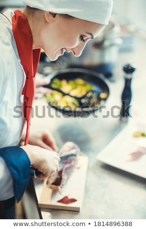 Chef cook in fancy restaurant kitchen slicing ham for a dish Stock photo © Kzenon