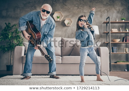 girls with guitar and microphone playing at home Stock photo © dolgachov