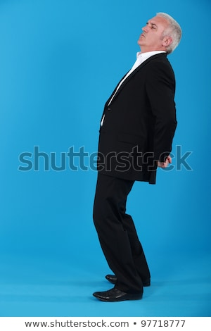 portrait of mature man standing back in profile against blue background Stock photo © photography33