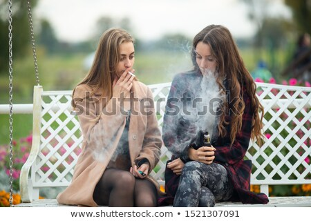 Young woman smoking cigarette on bench stock photo © diego_cervo
