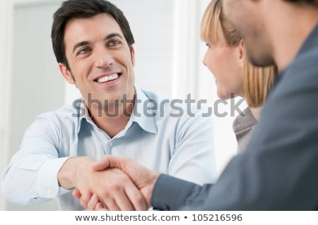 happy smiling business man shaking hands after a deal with a cus stock photo © dacasdo