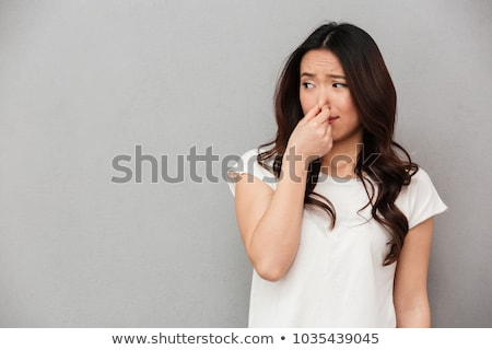 Disgusted woman pinching nose Stock photo © ichiosea