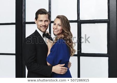 embraced elegant fashion couple standing in studio stock photo © feedough