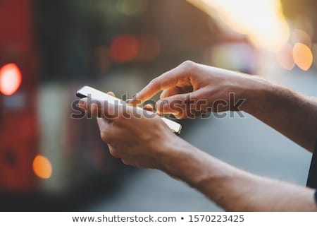 handsome young man typing a message on mobile phone stock photo © deandrobot