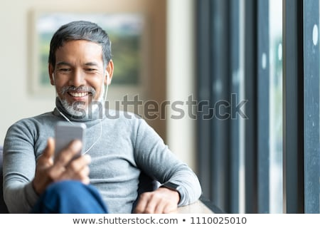 Portrait of a happy satisfied man listening to music Stock photo © deandrobot
