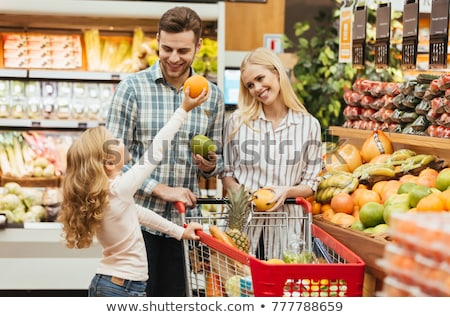 Happy young family with a child standing with a trolley Stock photo © deandrobot