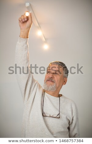 Senior man installing a ceiling light n a freshly renovated appartment Stock photo © lightpoet