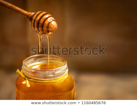 Natural sweet golden dripping honey in a glass pot with dipper on a gray stone table. Rosh hashanah  Stock photo © artjazz