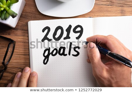 person writing 2019 year goals on dotted notebook stock photo © andreypopov