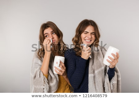 Image of two ill women covered with blanket drinking hot tea fro Stock photo © deandrobot