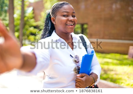 Beautiful young woman student in the park holding copybook talking by phone. Stock photo © deandrobot