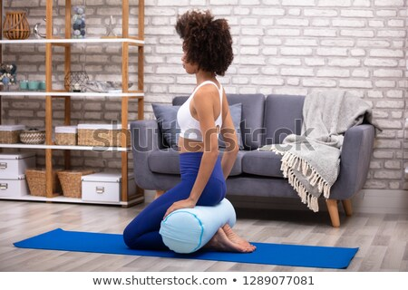 Young Woman Sitting On Exercise Mat Balancing On The Cushion Stock photo © AndreyPopov