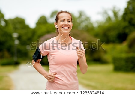 woman with earphones and armband at park Stock photo © dolgachov