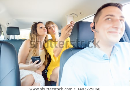 Women in taxi taking selfies with their phones Stock photo © Kzenon