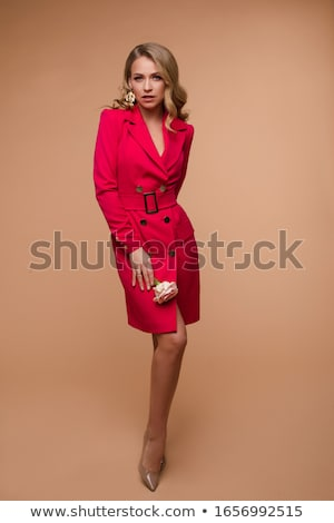 Stock photo: Stunning slim model in bright red dress and black heels.