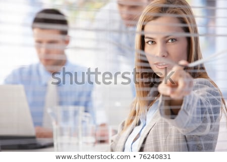 Beautiful businesswoman peeping through blind Stock photo © nyul