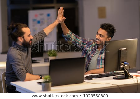 creative team making high five at night office stock photo © dolgachov