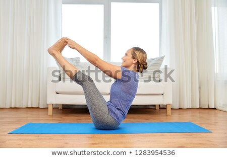 woman doing yoga double toe hold pose at home Stock photo © dolgachov