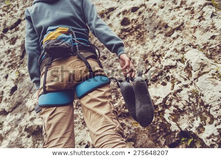 Rear view of young female climber standing in front of climbing wall with rocks Stock photo © pressmaster