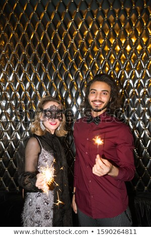 Glamorous girl in venetian mask and elegant guy with sparkling bengal lights Stock photo © pressmaster