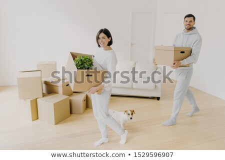 Photo of happy smiling brunette woman and her husband carry cardboard boxes with personal belongings Stock photo © vkstudio