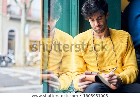 man with notebook or diary writing on city street Stock photo © dolgachov