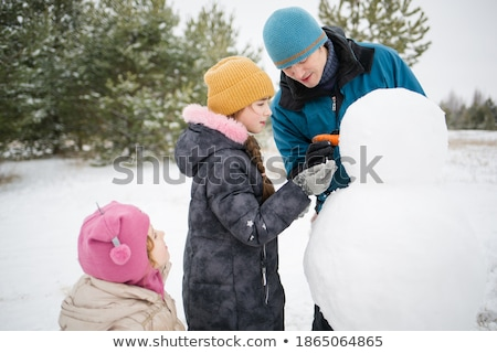 Father and Children Sculpting Snowman Outdoors Stock photo © robuart