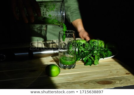 Man pouring in glass healthy detox smoothie, cooking with blender Stock photo © Illia
