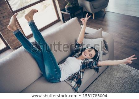 young girl enjoys listening music in headphones lying on sofa stock photo © hasloo