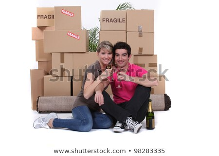 Stock photo: Couple surrounded by belongings and drinking champagne