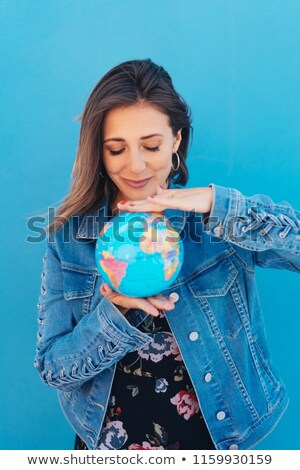 Stock photo: Woman with a globe balanced between her hands