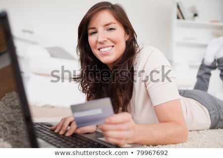 young beautiful woman making a payment with a credit card on the internet while lying on a carpet in stock photo © wavebreak_media