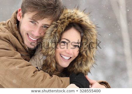 Young Beautiful Couple Smiling Outdoors in Snowy Winter Stock photo © maxpro