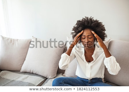 Young woman with headache holding her forehead Stock photo © pablocalvog