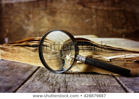 magnifying glass on a pile of open books stock photo © borysshevchuk